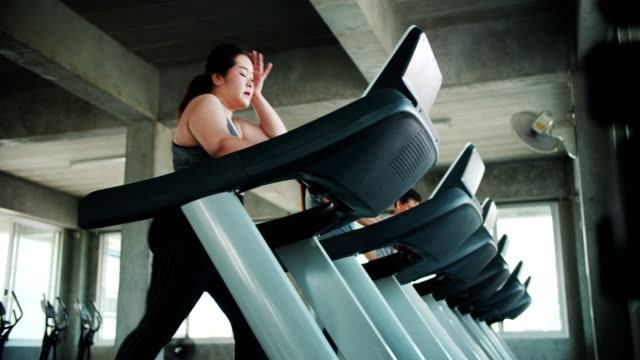 Larger woman exhausted by exercising on treadmill Handheld shot of asian larger woman exhausted by exercising on treadmill in gym, Bangkok Thailand health club stock videos & royalty-free footage