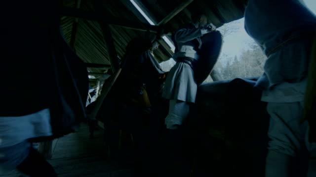 vídeos y material grabado en eventos de stock de recreación de la batalla medieval a gran escala. guardias en la pared de la fortaleza de madera prepárate repeler el ataque. su lucha con hachas, espadas, lanzas, arcos y escudos. - vikingo