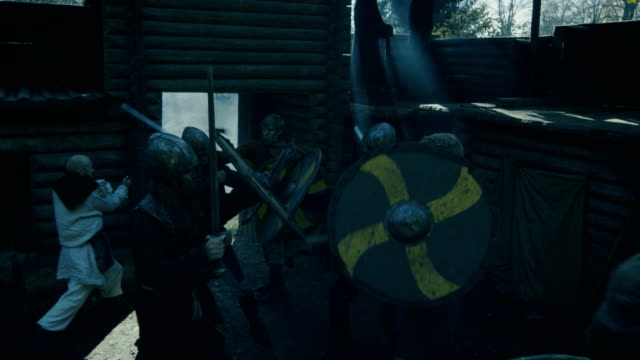 large-scale medieval battle reenactment. viking and slav warriors fight with swords, axes and shields in the yard of the wooden fortress. - битва стоковые видео и кадры b-roll