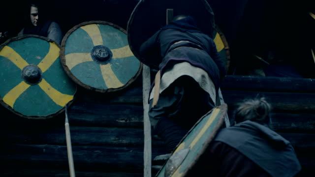 vídeos y material grabado en eventos de stock de recreación de la batalla medieval a gran escala. violenta tribu de guerreros atacan la fortaleza de madera pared, suben escaleras, protectores de intentan defender fortification.they lucha con hachas, espadas, lanzas, arcos y escudos. - vikingo