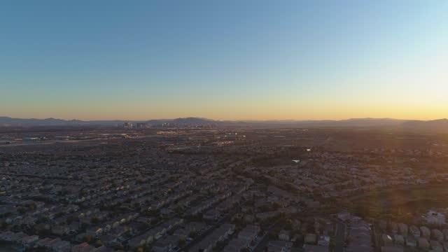 vidéos et rushes de horizon de las vegas au lever du soleil. centre-ville et quartier résidentiel. nevada, etats-unis. vue aérienne. drone vole vers le haut - inclinaison vers le haut