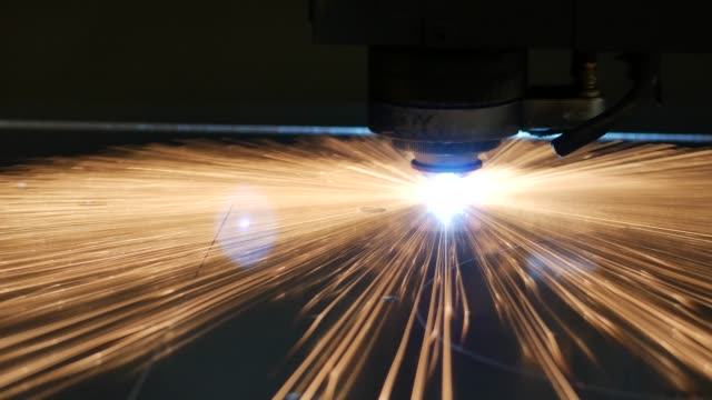 laser cut machine while cutting the sheet metal with sparks and high precision - inarcare la schiena video stock e b–roll
