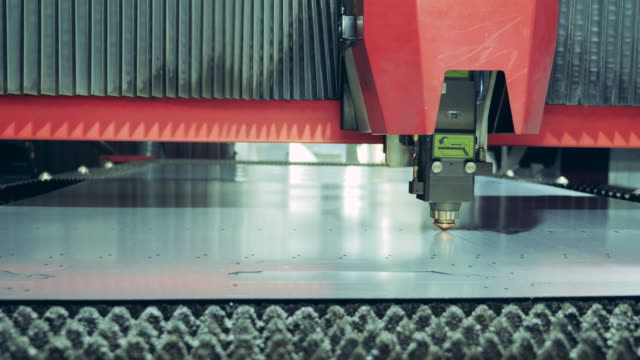 laser cutter is processing a piece of metal - нержавеющая сталь стоковые видео и кадры b-roll
