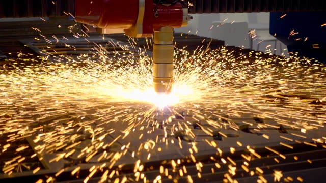 Laser cutting of metal. Sparks fly around.  Slow mo, slo mo video