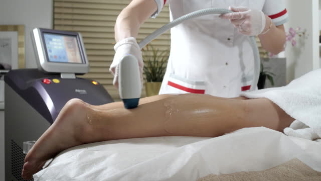 Laser epilation and cosmetology. Hair removal on ladies legs. at cosmetic beauty spa clinic. Cosmetology procedure from a therapist video