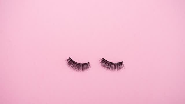 Lashes loss and extension concept. Fake eyelashes fall on trendy pastel pink background. Makeup accessories. Cosmetic products. Top view. Stop motion animation. Beauty pattern. Looping video. Lashes loss and extension concept. Fake eyelashes fall on trendy pastel pink background. Makeup accessories. Cosmetic products. Top view. Stop motion animation. Beauty pattern. Looping video. eyelash stock videos & royalty-free footage