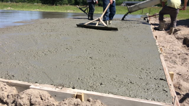 Last bit of concrete being poured to form slab as workers push it around with hand tools