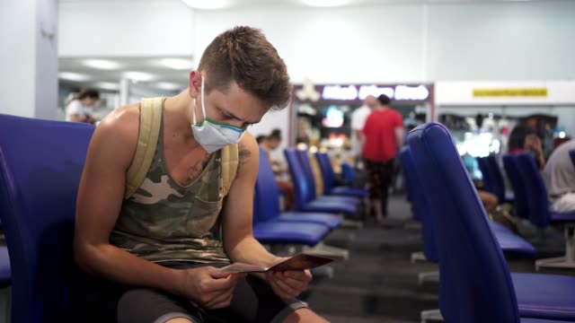 Last check before flight Young man with protective mask is checking one more time his passport and ticket while sitting in the airport waiting room. passport stock videos & royalty-free footage