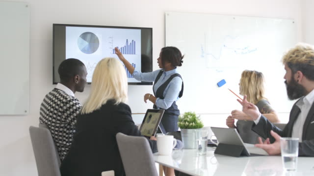Last year was our best Group of young start-up entrepreneurs is sitting in an office. They are having meeting. Woman is showing some graphs to her coworkers. presentation stock videos & royalty-free footage
