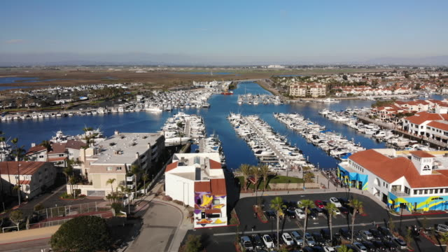 vídeos de stock e filmes b-roll de late afternoon drone footage of huntington harbour in southern california los angeles close to the pacific ocean and huntington beach - estrada 001
