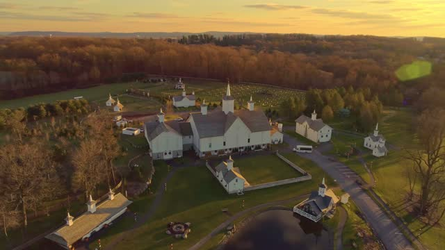 Late Afternoon Fall Aerial View with Sun Rays of Beautiful Restored Barns and Countryside