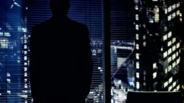 Late at Night Businessman Stands at the Window in His Office with Big City View. Late at Night Businessman Stands at the Window in His Office with Big City View. Shot on RED EPIC-W 8K Helium Cinema Camera. baltic countries stock videos & royalty-free footage