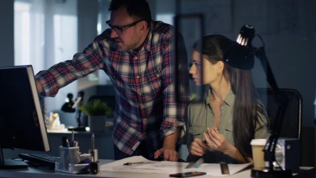 sent på natten i ingenjörs firma, manliga och kvinnliga kollegor arbeta med utkast med hjälp av dator. bordet lyser med lampa. - man architect computer bildbanksvideor och videomaterial från bakom kulisserna
