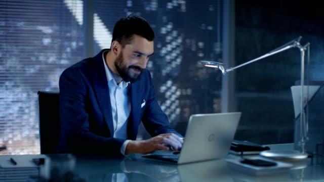 spät in der nacht im privaten büro geschäftsmann arbeitet an einem laptop lächeln vor der kamera. im hintergrund großstadt fensteransicht. - börsenhandel finanzberuf stock-videos und b-roll-filmmaterial