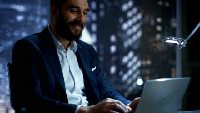 Late at Night in Private Office Businessman Works on a Laptop. He Succeeded Internationally by Winning Big Contract. He's Very Happy. Late at Night in Private Office Businessman Works on a Laptop. He Succeeded Internationally by Winning Big Contract. He's Very Happy. Shot on RED EPIC-W 8K Helium Cinema Camera. financial occupation stock videos & royalty-free footage