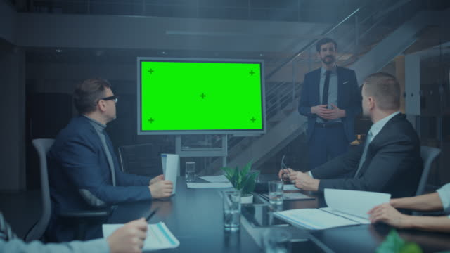 late at night in the corporate meeting room: director talks and uses digital chroma key interactive whiteboard for presentation to executives, investors. green mock-up screen in horizontal mode - conferenza stampa video stock e b–roll