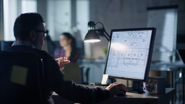 事務所で夜遅く。設計エンジニアは、自分のパソコンで動作します。彼の展示は、設計図を参照してください。オフィスは近代的に見えます。背景の人々 は働きます。 - クリエイティブな職業点の映像素材/bロール