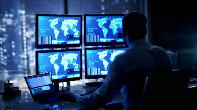 geç gece güvenlik operatör dikkatle üzerinde gösterilen konumu hassas bilgileri onun monitörlerle gözlemler. - kesit stok videoları ve detay görüntü çekimi