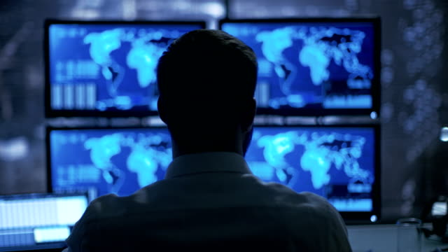 Late at Night Security Operator Attentively Observes His Monitors with Location Sensitive Information Shown on Them. video