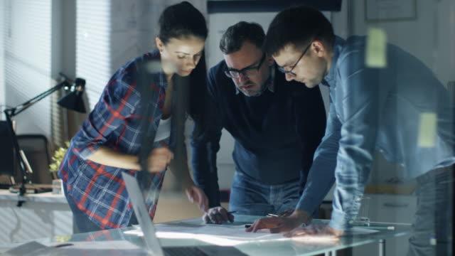 vídeos de stock, filmes e b-roll de tarde na equipe da noite de engenheiros de design coletivamente trabalhar no project. they inspecionar rascunhos, documentos, fazer correções e ter discussão na mesa grande. - perfeição