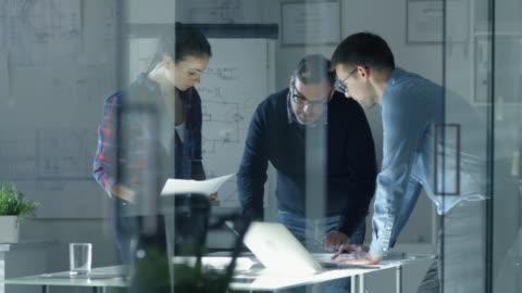 vidéos et rushes de tard dans l'équipe de nuit des ingénieurs de conception travailler sur un projet. ils travaillent sur une table de conférence éclairée avec des documents, des blueprints et un ordinateur portable sur elle. - architecte