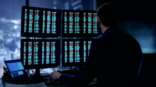 late at night trader reads number on his multiple displays with stock information on them. in background big city window view. - stock broker stock videos & royalty-free footage