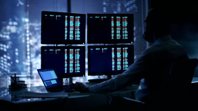 Spät liest bei Nacht Trader Zahlen auf seiner mehrere Displays mit Börsendaten, berät er auch Kunden mit Kopfhörer auf. Im Hintergrund Großstadt Fensteransicht. – Video