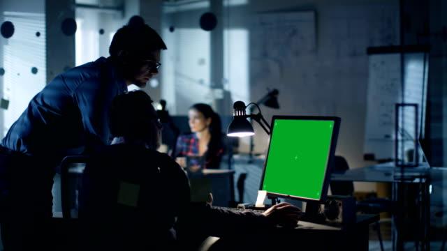 i̇ki endüstri mühendisleri tartışma var gece geç saatlerde, kişisel bilgisayar izole yeşil ekran mock-up ekran gösterir. ofis modern planları duvarlara dolu görünüyor. - masaüstü bilgisayar stok videoları ve detay görüntü çekimi