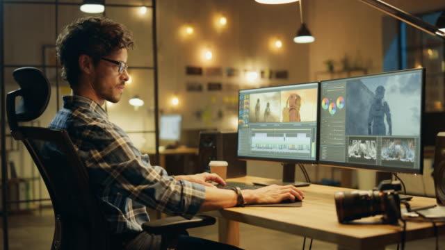 深夜クリエイティブオフィス:プロのカラースト/写真は、画像編集ソフトウェアを使用して、フォトモンタージュを行い、デスクトップコンピュータ上で動作します。モダンなスタイリッシ� - 編集者点の映像素材/bロール