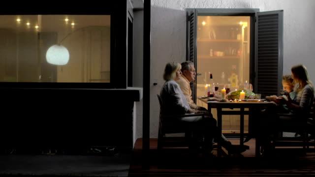 Später Familie Abendessen im Freien auf der Terrasse – Video