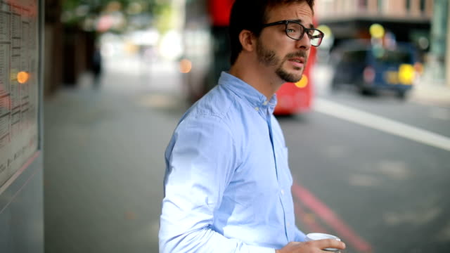 Late for work Young nerdy man looking at the map and waiting for the transportation in London, UK bus stop stock videos & royalty-free footage