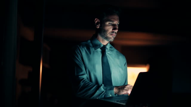 Late night working man using laptop in the dark video