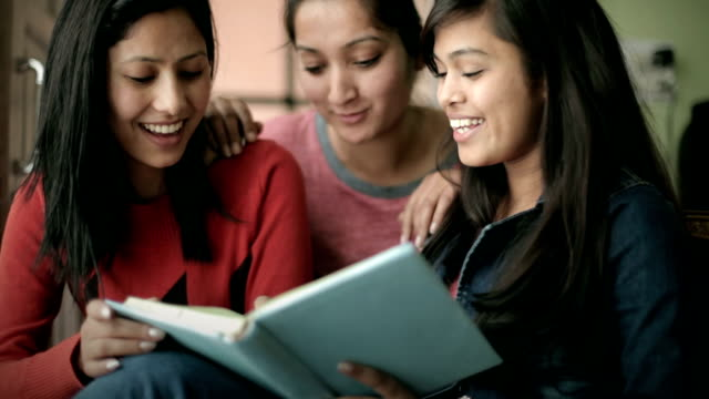 Late teen happy girl students studying a book together. video