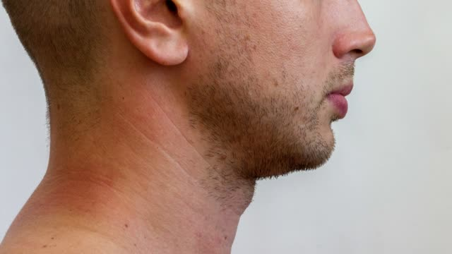 lateral part of the male face growing beard of young caucasian man - barba peluria del viso video stock e b–roll