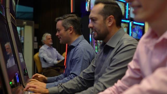 Latin America adult man playing at the casino on slot machines celebrating a win