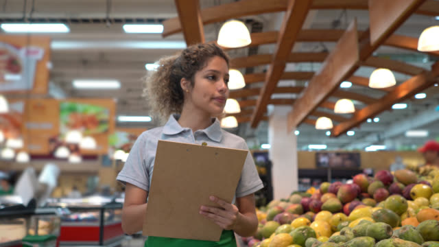 Latin American beautiful saleswoman checking the fruit retail display and inventory on clipboard