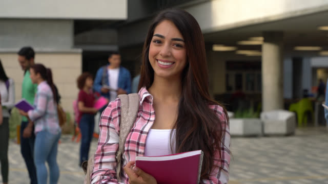 latin amerikalı güzel öğrenci üniversite kampüsünde gülümseyen kameraya bakarken defterlerini tutarak - kolombiya stok videoları ve detay görüntü çekimi