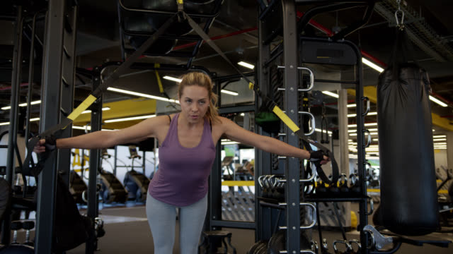 Latin American beautiful woman working out at the gym using suspension straps