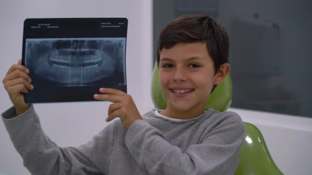 latin amerikalı çocuk diş hekimi sandalyesinde otururken kameraya gülümseyerek dişlerinin bir xray tutarak - diş sağlığı stok videoları ve detay görüntü çekimi