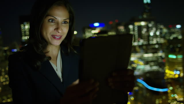 Latin American businesswoman rooftop video call at night video