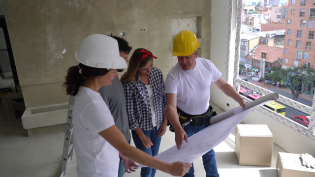 latin american contractors showing young couple a blueprint while explaining something during a home renovation - imprenditore edile video stock e b–roll