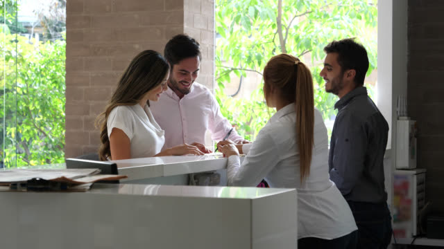 latin american couple arriving to the hotel at the front desk talking to manager and receptionist - hotel checkin video stock e b–roll