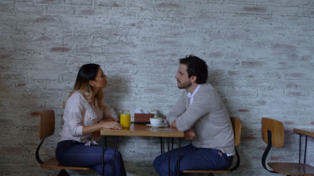 latin american couple on a date at a bakery enjoying juice and coffee talking while waitress brings a croissant - cucina francese video stock e b–roll