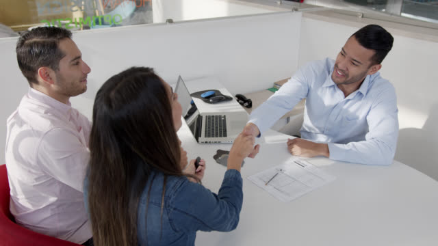 Latin American couple signing a form at a car dealership and handshaking with friendly salesman Latin American couple signing a form at a car dealership and handshaking with friendly salesman all smiling car salesperson stock videos & royalty-free footage