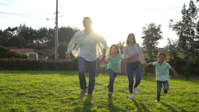 stockvideo's en b-roll-footage met latijns-amerikaanse paar met hun twee kinderen die handen vasthouden en rennen in hun achtertuin erg blij - garden house
