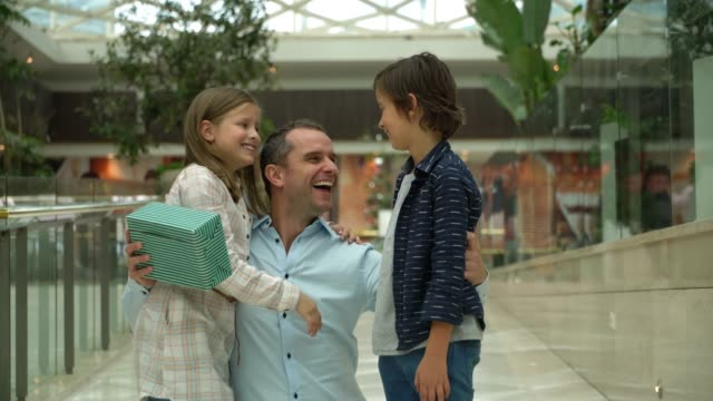 latin american cute daughter and son surprising their dad at the mall with a present for father's day - fathers day stock videos and b-roll footage