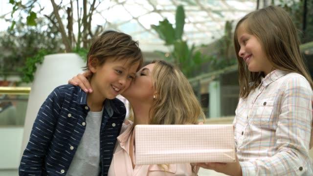 ラテンアメリカのかわいい娘と息子は母の日のプレゼントとモールで彼らのお母さんを驚かせる - 母の日点の映像素材/bロール
