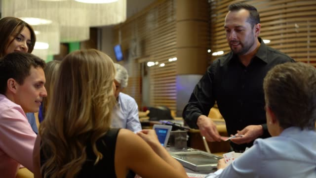 Latin American dealer at the black jack table dealing cards to a group of people at a casino