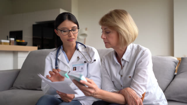 Latin American doctor giving a prescription and medicine to senior patient at her home Latin American doctor giving a prescription and medicine to senior patient at her home – Lifestyles female doctor stock videos & royalty-free footage