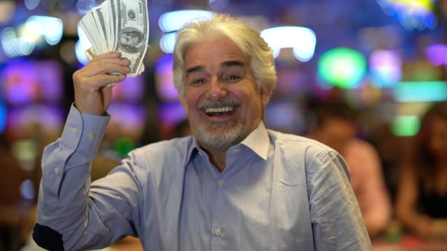 Latin American elder man holding a bunch of money while looking and laughing to camera at the casino
